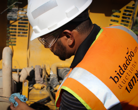 bidadoo Production Lead checking oil level on heavy equipment.
