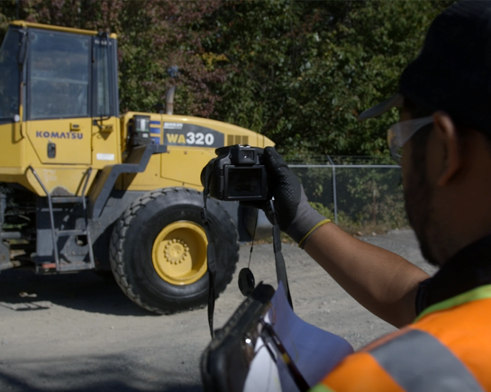 A bidadoo employee photographing a Komatsu Wheel Loader as a part of the equipment production process